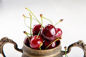 Juicy wet cherries in brass vessel
