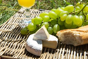 Picnic concept - orange juice, baguette, cheese and grapes