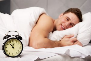 Man with alarm clock in bedroom.