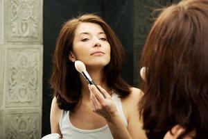 Beautiful woman brushing her cheek.