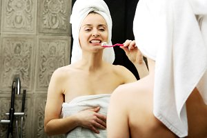 Woman brushing teeth in bathroom.