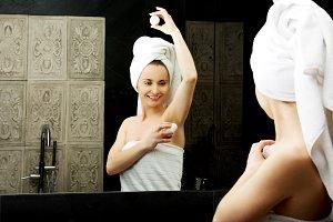Woman using deodorant.