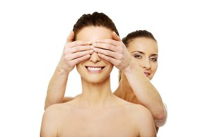 Woman covering friend's eyes.