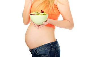 Pregnant woman holding a bowl with salad