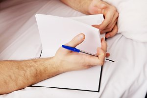 Man writing a note in bed.
