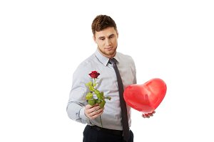 Young man with a red rose and heart balloon.