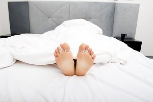 Bare woman's feet in bedroom.