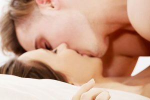 Young couple kissing on bed.
