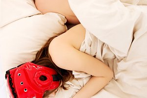 Woman sleeping in protective helmet.