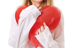 Young woman with heart shaped balloon.