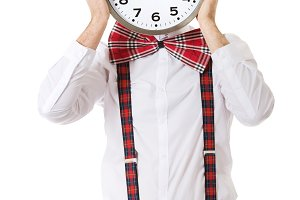 Man wearing suspenders hiding behind big clock.