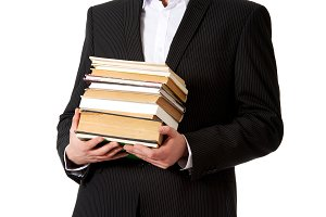Young businessman holding stack of books.