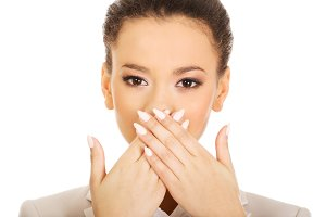 Businesswoman covering mouth with hands.