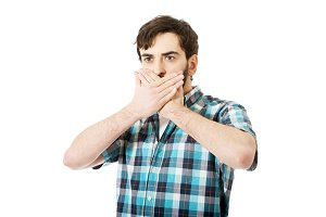 Young shocked man covering his mouth.