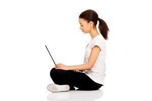 Teen sitting cross legged with laptop.