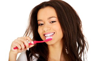 Beautiful teen brushing her teeth.
