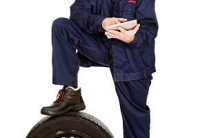 Smiling mechanic with a tire and tablet