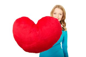 Young woman with heart shaped pillow