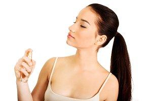 Young woman applying parfume.