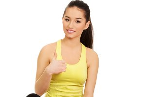 Fitness woman sitting on exercise mat.