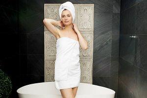Beautiful woman standing near bathtub.