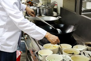 Chef in hotel or restaurant kitchen busy cooking