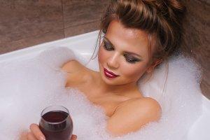 Girl is drinking wine in bathtub