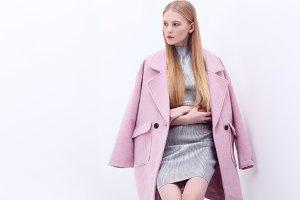 Young elegant woman in pink coat.
