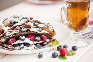 Pancakes with blueberries and raspberries, mascarpone cream and tea