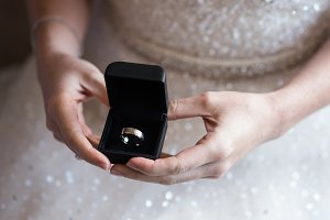 Bride holding grooms wedding ring
