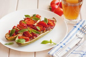 Vegetarian food. Baked zucchini with tomato and basil