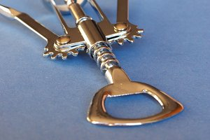 corkscrew and bottle opener over blue