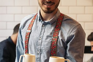 Waiter holding a tray with coffees.