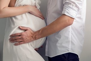 pregnant girl and her husband standing