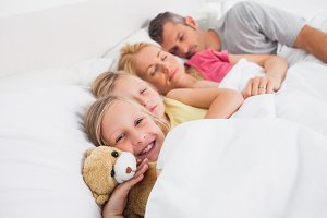 Parents sleeping with their daughters in bed