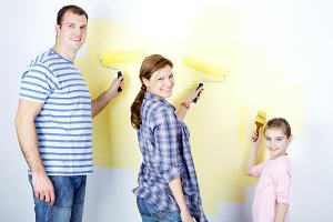 Happy family painting the wall.