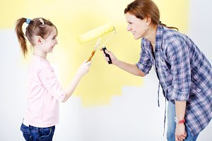 Mother and daughter painting a wall.
