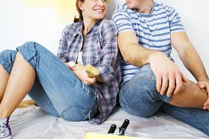 Happy couple sitting on the floor after painting their home.