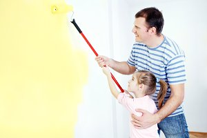 Father and daughter painting a wall.
