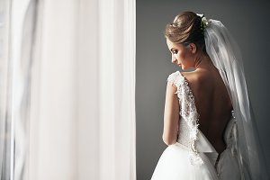 The bride stands near window