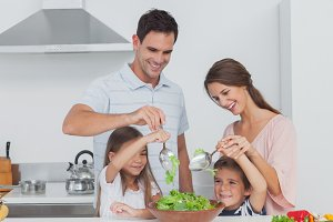 Family mixing a salad together