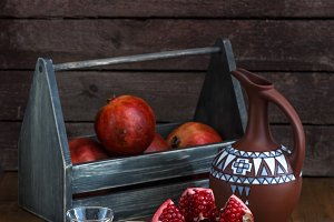 Ripe pomegranate fruit with pomegranate juice on copper plate and fruit box and jug on wooden vintage table.