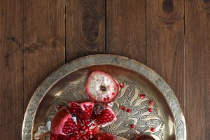 Ripe pomegranates with juice on copper plate on wooden background, top view
