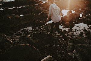 Girl walking along rocky beach