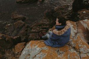 Girl Sitting on a Boulder