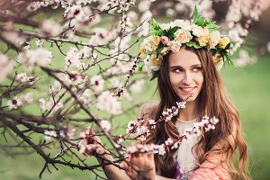 Beautiful girl among the branches of blossom cherry tree