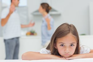 Upset girl listening to parents quarreling