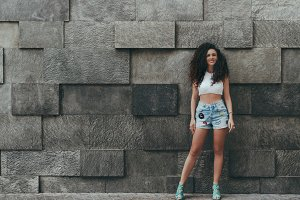 Curly girl in front of textured wall