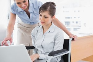 Disabled businesswoman showing co worker her laptop