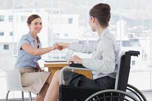 Businesswoman shaking hands with disabled colleague